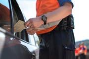 Ein Polizist kontrolliert Fahrzeugpapiere und Fahrausweis eines Autofahrers. (Bild: Keystone)