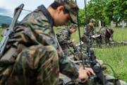 In der Infanterie kann man den Dienst an einem Stück absolvieren. Das Bild zeigt Rekruten dieser Truppengattung, die bei einer Übung Funkgeräte einstellen. (Symbolbild Keystone/Christian Beutler)
