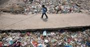 Spuren der Wegwerfgesellschaft: Ein Junge passiert auf seinem Schulweg in der indischen Hauptstadt Neu-Delhi eine Mülldeponie. (Bild: Rajat Gupta/AP (22. April 2017))