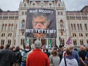 """An der Abstimmung nahmen nur rund 45 Prozent der Wähler teil, für einen gültigen Ausgang wären 50 Prozent nötig gewesen. """"Was habe ich wieder getan"""" steht auf dem Poster mit Premier Orban an einer Protestveranstaltung der Opposition in Budapest. (Bild: KEYSTONE/AP/VADIM GHIRDA)"""