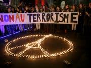 Das etwas abgeänderte Peace-Zeichen mit dem Eiffelturm im Kreis wird zum Symbol für die Solidarität mit den Opfern der Anschläge in Paris. (Bild: /KEYSTONE/SALVATORE DI NOLFI)