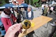 Bürger hefteten sich am Samstag einen solchen Button an und wehrten sich damit gegen die Poststellenschliessung. (Bild: urh (Wassen, 20.5.2017))