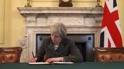 Auf einem offiziellen Foto ist zu sehen, wie die britische Premierministerin May den Brief an die EU unterzeichnet. (Bild: RTÉ News / Twitter)