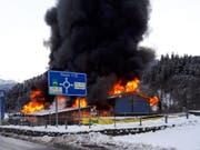 Meterhohe Flammen und eine dicke Rauchsäule: Das Landi-Gebäude in Thusis GR steht in Vollbrand. (Bild: Fabiana Calsolaro, sda)