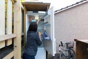 Eine Studentin nimmt Nahrungsmittel aus einem öffentlichen Kühlschrank im Hinterhof des Lola-Ladens, am Mittwoch, 8. April 2015 in Bern. (Bild: Keystone/ Peter Klaunzer)