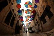 Muslime auf der ganzen Welt feiern den Ramadan. Im Bild: Ein Eingang zur Altstadt von Nablus wurde mit farbigen Schirmen verziert um den Fastenmonat Ramadan einzuläuten. (Bild: EPA/ALAA BADARNEH)