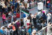 Fluggäste schlängeln sich zu Beginn der Sommerferien am Flughafen Zürich zum Check-In. (Bild: Keystone)
