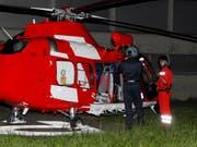 Ein Mitarbeiter der Schwyzer Polizei (links) macht sich bereit für den Flug im Rega-Heli. (Bild: Geri Holdener)