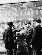 DDR-Arbeiter vor einer Wandtafel in einer Brikettfabrik. (Bild: Keystone (1952))