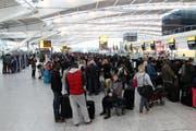 Passagiere stehen vor den Check-In Schaltern am Londoner Flughafen Heathrow Schlange. (Bild: Keystone)