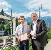 Fabio Setto mit seinem Arbeitsgerät (Rasenmäher) und Bildungsdirektor Franz Enderli, aus dessen Händen er das Diplom im Hüetli-Garten erhält. (Bild: Christoph Riebli (Sarnen, 4. Juli 2017))