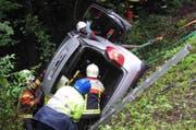 Das Auto kam in Schräglage zum Stillstand. Mitglieder der Feuerwehr Arth bergen den Fahrer aus dem Wagen. (Bild: Kantonspolizei Schwyz)