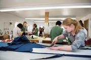 Seraina Waser (vorne rechts) schneidet im Atelier einen Stoff zu (Bild: Corinne Glanzmann (Stans, 14. März 2018))
