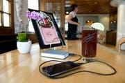 Ein Handy wird im Restaurant über einen portablen Akku geladen. (Bild: Corinne Glanzmann)