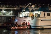 Einsatzkräfte der Feuerwehr kletterten auf das havarierte Hotelschiff aus der Schweiz. Bei der Kollision des Schiffs mit einem Brückenpfeiler bei Duisburg wurden mehrere Personen zum Teil schwer verletzt. (Bild: Marcel Kusch/DPA)