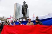 Pro-russische Demonstranten bilden eine Russkand-Fahne unter der Statue von Vladimir Lenin. (Bild: AP / Andrey Basevich)