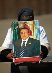 Eine Unterstützerin hält während eines Protests ein Porträt von Ägyptens Ex-Präsident Hosni Mubarak. (Bild: Khalil Hamra/AP (Kairo,)