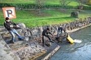 Helfer ziehen einen schweren Metallwagen aus dem Wasser. (Bild: PD)