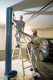Walti von Büren von der Weidli-Werkstätte streicht zusammen mit Giulia Baudat von der Malerei Schmid AG eine Säule in einem Parkhaus des Bürgenstock-Resorts. (Bild: Corinne Glanzmann (Bürgenstock, 11. Juli 2017))