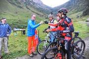 Stabsübergabe auf rund 1300 Metern über Meer: Das Bike-Team um Linda Indergand überreicht SBB-CEO Andreas Meyer (links) auf der Alp Hinter Etzliboden einen Teil des Kunstwerks, das später in Sedrun zusammengeführt wird. (Bild Urs Hanhart)
