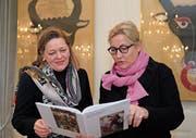 Heidi Z'graggen und Buchautorin Marion Sauter begutachten das Werk. (Bild: Florian Arnold (Altdorf, 28.11.2017))