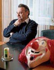 Der Sarner Pfarrer Bernhard Willi im Pfarrhaus mit einer Maske, die er für Bekannte aufbewahrt. An der Fasnacht trägt er selber keine Masken – «man kennt mich». (Bild: Corinne Glanzmann (Sarnen, 7. Februar 2017))