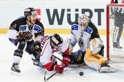 Team Canadas Chris Didomenico, Mitte, kämpft um den Puck mit Luganos Goalie Elvis Merzlikins und Lorenz Kienzle. (Bild: Keystone/ Gian Ehrenzeller)