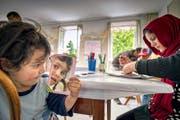 Ramisa (3) spielt mit einem Spiegel, Mutter Narges (25) widmet sich einer Zeichnung. Beide stammen aus Afghanistan. (Bild Christoph Riebli)