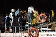 Einsatzkräfte der Feuerwehr bei der Evakuierung von Personen mit Rettungsdecken auf ein anderes Schiff. Ein Hotelschiff mit 129 Personen war am späten Dienstagabend auf dem Rhein mit einem Brückenpfeiler kollidiert. (Bild: Marcel Kusch/DPA)