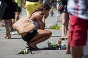 Eine Frau trauert an der Promenade des Anglais in Nizza. (Bild: EPA / Ian Langsdon)
