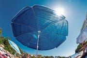 Selbst wenn der Sonnenschirm fast nichts durchlässt: UV-Strahlen haben auch im Schatten ihre Tücken. (Bild: Martin Moxter/Getty)