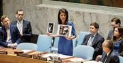 Nikki Haley, UNO-Botschafterin der USA, zeigt an der Sicherheitsratssitzung Bilder von Opfern des jüngsten Giftgas-Anschlags in Syrien.Bild: Justin Lane/EPA (New York, 5. April 2017)