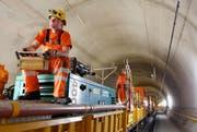 Arbeiter montieren Kupferdrähte für die Fahrleitung. (Bild: Keystone / Urs Flüeler)