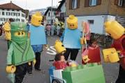 Drei Generationen Omlin als Lego-Männchen. Diyan als Ninjakrieger (ganz links im Bild), Niilo im Wagen und Tia ohne Maske. (Bild: Marion Wannemacher (Sachseln, 23. Februar 2017))