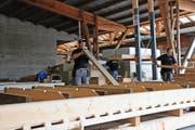 Ruedi Käslin (links) prüft in der Produktionsstrasse die Balken, bevor sie in die Lärmschutzwand eingebaut werden. (Bild Philipp Unterschütz)