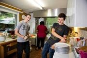 Die Lehrlinge Fabio Thon (links) und Raphael Stöcklin helfen «Schlummermutter» Daniela Buschor in der Küche. (Bild Corinne Glanzmann)