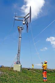 Präzisions- und Teamarbeit: Die Bodencrew platziert das Windrad, das noch am Helikopter hängt, auf dem Masten. (Bild Matthias Piazza)