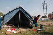 Eine Frau wäscht Ende November Kleider vor ihrem Zelt. Dieses befindet sich in einem Camp in Kathmandu, welches für die Überlebenden des Erdbebens im April erstellt wurde. (Bild: Keystone / Niranjan Shrestha)