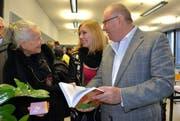 Alexandra Hürlimann (19) betrachtet mit Franz Scheuber (73) und Silvia Gessner (72) ihre Maturaarbeit zum Thema «Wertewandel in der Erziehung». (Bild: Romano Cuonz / Neue NZ)