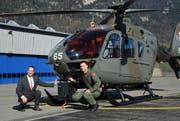 Systemplaner und Projektleiter des DVE-Projektes Samuel Allemann (links) und der Pilot Michael Hügli knien vor dem von der Schweizer Luftwaffe für das Projekt «Fliegen bei schlechten Sichtverhältnissen» ausgerüsteten EC 635.
