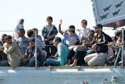 Flüchtlinge warten auf einem italienischen Navy-Schiff im Hafen Pozzallos. (Bild: Keystone)