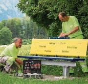 Die Werkdienstmitarbeiter Gody Durrer (links) und Daniel Michel montieren an der Zubenstrasse in St. Niklausen eine der zwanzig gelb- blauen Sitzbänke. (Bild: PD)