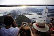 Touristen beobachten vom Zuckerhut aus den Sonnenuntergang. (Bild: Getty)