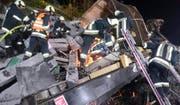 Feuerwehrleute setzen auf einem mit Bahnschwellen beladenen, zerstörten Wagen Schneidbrenner ein. (Bild: Keystone/APA/Freiwillige Feuerwehr Brixen)