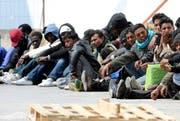 Migranten warten im April 2011 auf ein Schiff, welches Sie von Lampedusa aufs Festland bringen soll. (Bild: Keystone / Archiv)
