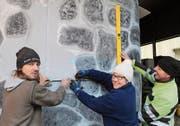 Marcel Zgraggen, Sandra Indergand und Erich Furrer (von links) zeichnen auf der Vorderseite des Wagens ein Fenster für den Fahrer ein. (Bild: Markus Zwyssig (Erstfeld, 3. Februar 2018))