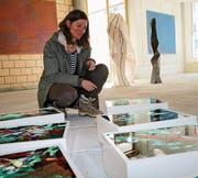 Mireille Tscholitsch vor ihren Bildern mit Kois, hinten Werke von Gertrud Guyer Wyrsch. (Bild: Marion Wannemacher (Stans, 8. März 2018))