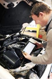 Ein Experte (mit Tablet in der Hand) blickt in der Prüfhalle des VSZ in Stans unter eine Motorhaube. (Bild Corinne Glanzmann)