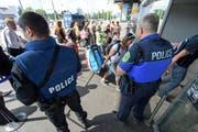 Polizisten bewachen Personen beim Eingang in Genf. (Bild: Keystone / Martial Trezzini)