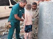 Sicherheitskräfte kümmern sich um Emad Tamo. Der Junge ist völlig unterernährt und voller Staub. (Bilder: Cedric Rehman)